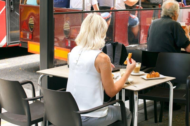 Mujer que se sienta en un café de consumición del café de la calle y que mira la vida de ciudad, forma de vida de Europa fotos de archivo libres de regalías