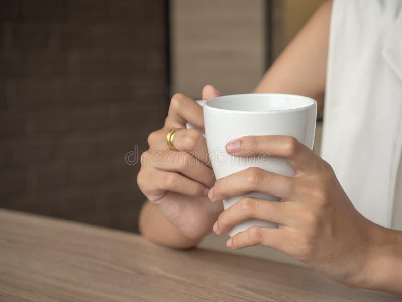 Mujer que se sienta en un café por la mañana y suavemente que sostiene una taza de café disponible fotografía de archivo