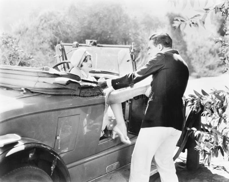 Mujer que se sienta en un convertible que golpea y que empuja a un hombre con el pie lejos (todas las personas representadas no s fotos de archivo libres de regalías
