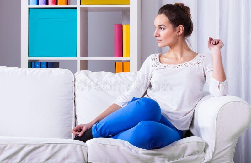 Mujer que se sienta en un sofá imagenes de archivo