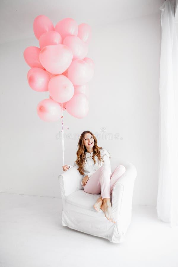 Mujer que se sienta en una butaca y que sostiene un manojo de globos rosados fotografía de archivo libre de regalías