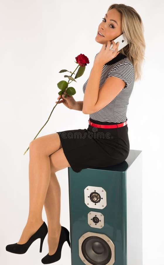 Mujer que se sienta en una caja de altavoz con una rosa en su mano y que habla con el iPhone imagen de archivo