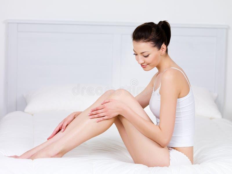 Mujer que se sienta en una cama y que frota ligeramente sus piernas imagenes de archivo