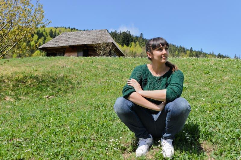Mujer que se sienta en una montaña verde fotos de archivo libres de regalías