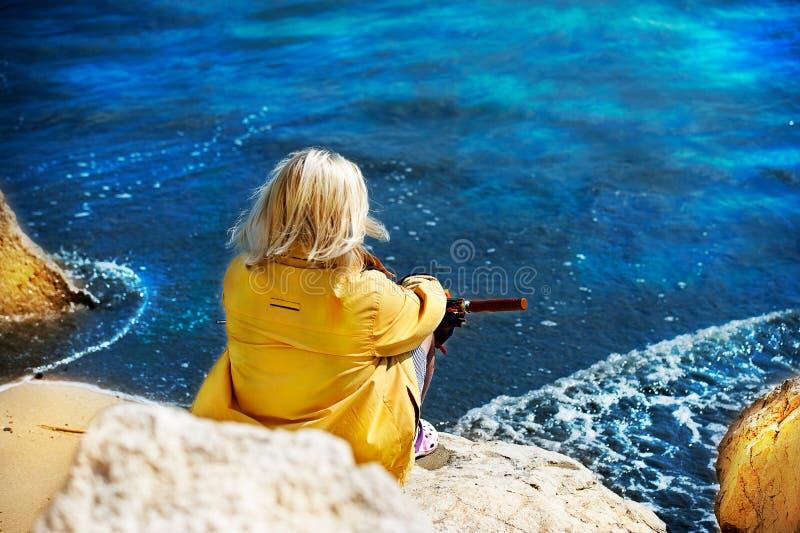 Mujer que se sienta en una roca por el mar fotos de archivo