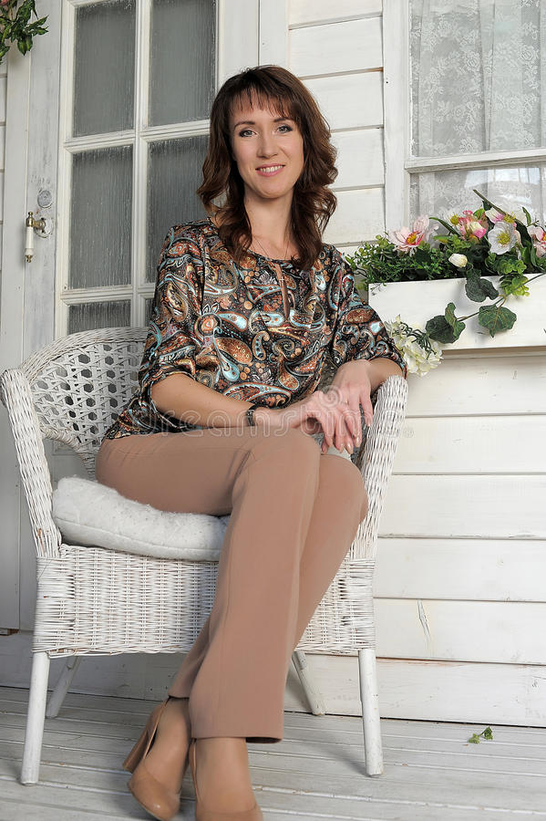 Mujer que se sienta en una silla de mimbre fotos de archivo