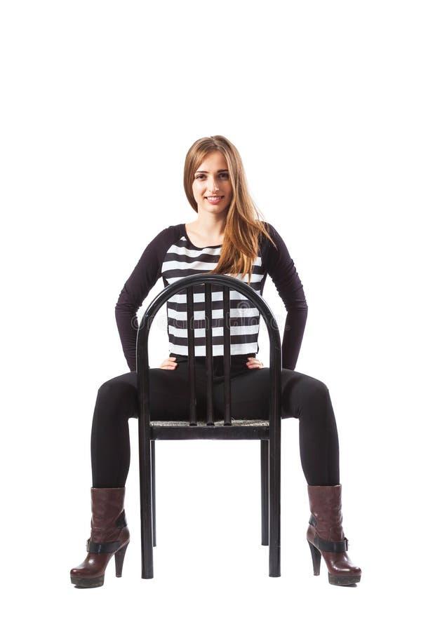 Mujer que se sienta en una silla y que lleva a cabo las manos en caderas foto de archivo libre de regalías