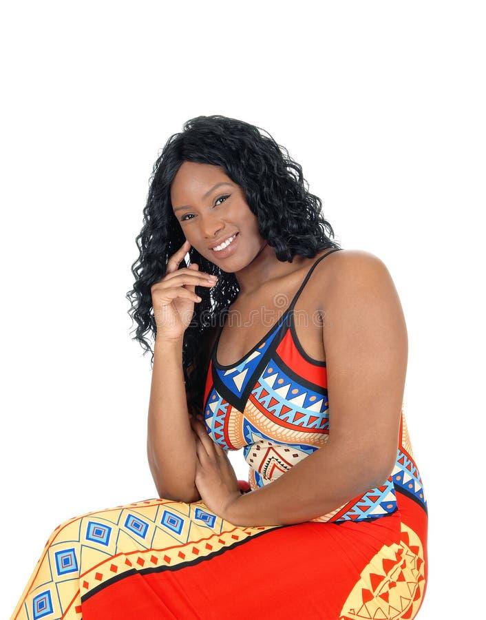 Mujer que se sienta en vestido colorido fotografía de archivo libre de regalías