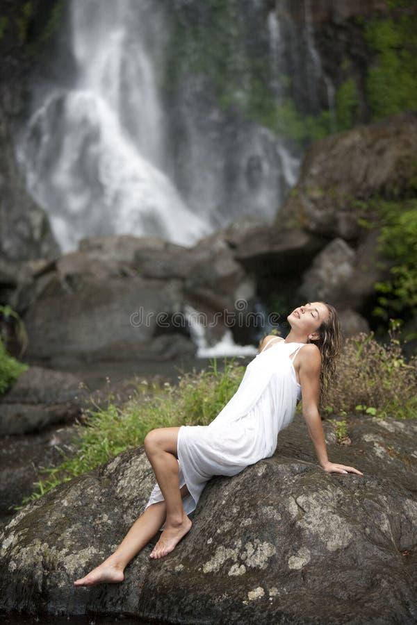 Mujer que se sienta por caídas foto de archivo