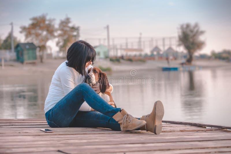 Mujer que se sienta por el río con su perro y que habla en el teléfono fotos de archivo