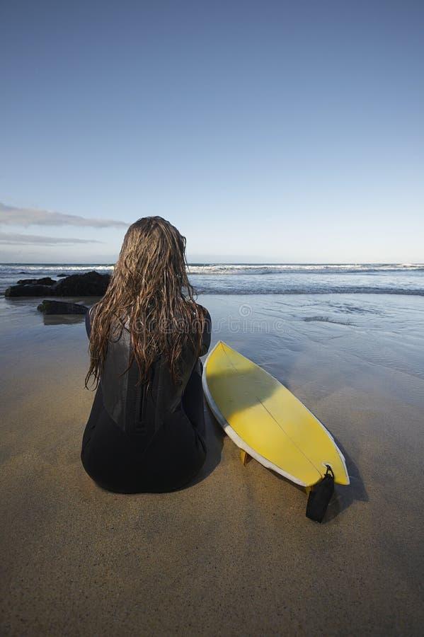 Mujer que se sienta por la tabla hawaiana en la playa fotografía de archivo libre de regalías