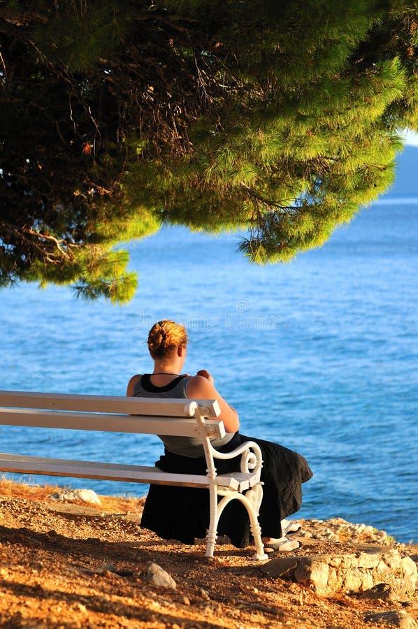 Mujer que se sienta solamente por la playa fotos de archivo libres de regalías