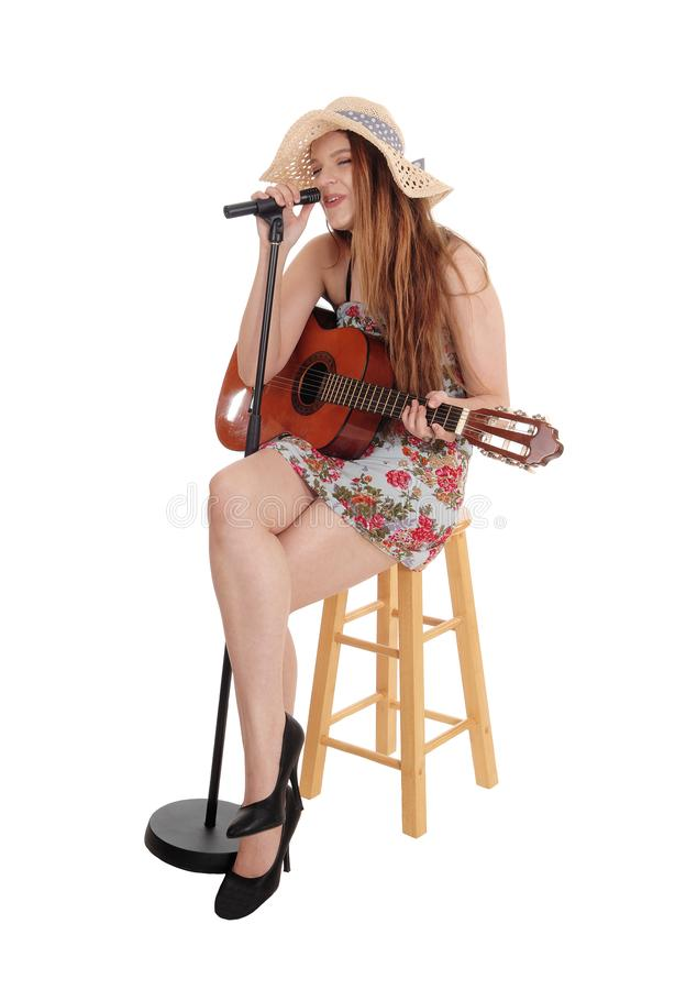 Mujer que se sienta tocando la guitarra y cantando imagen de archivo