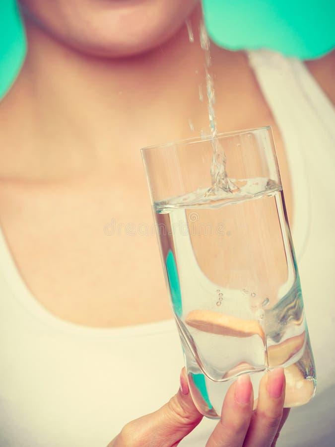 Mujer que se sostiene de cristal con agua y la tableta efervescente fotografía de archivo