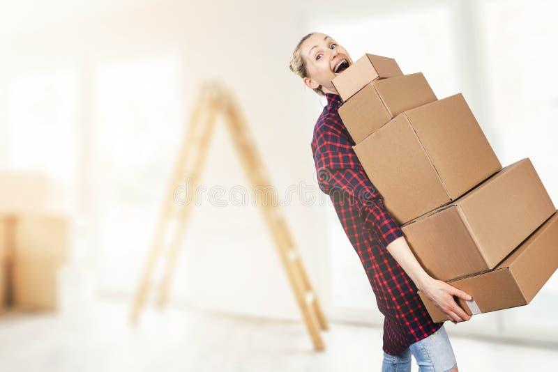 Mujer que se traslada a la nueva pila de la tenencia del apartamento de cajas de cartón imágenes de archivo libres de regalías