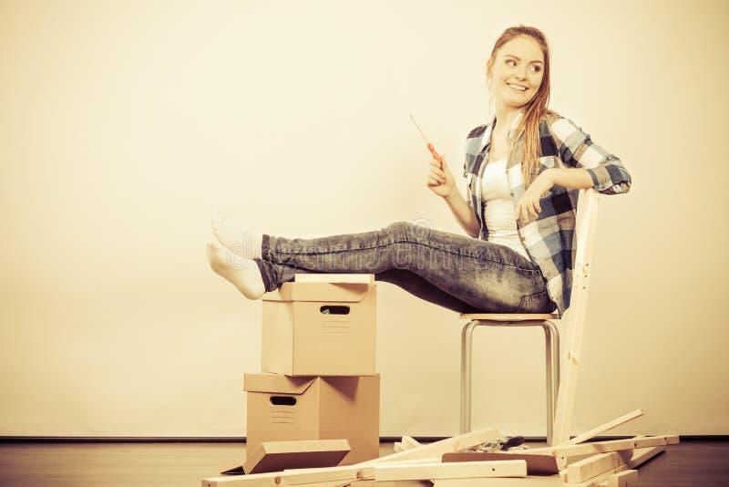 Mujer que se traslada a los muebles del montaje del apartamento imagenes de archivo