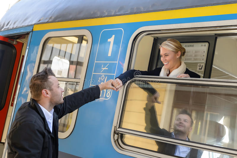 Mujer que se va con el hombre del tren que lleva a cabo la mano fotos de archivo