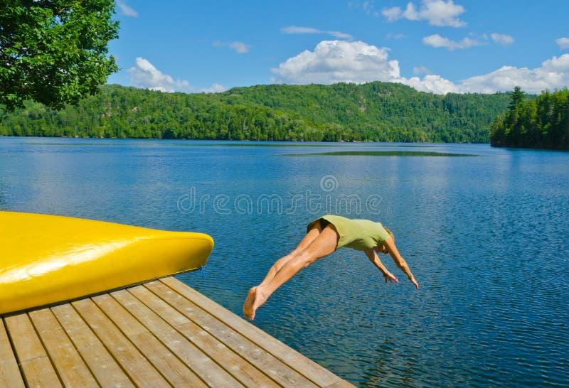 Mujer que se zambulle del muelle en el lago en un día de verano caliente foto de archivo