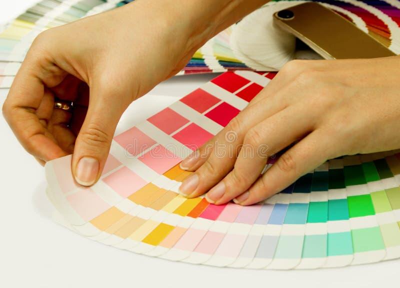 Mujer que selecciona color de las muestras de Pantone foto de archivo