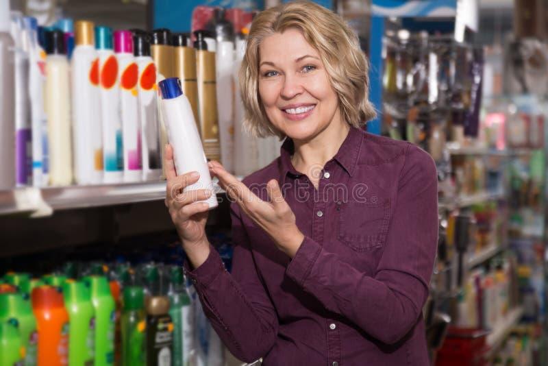 Mujer que selecciona la botella de champú fotos de archivo