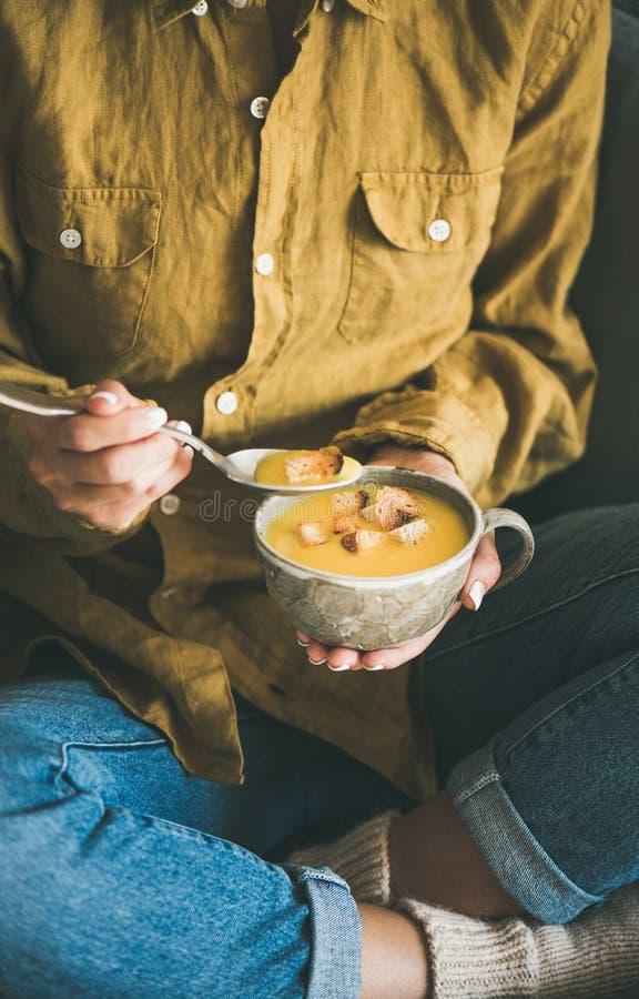 Mujer que sienta y que come la sopa de la calabaza de la taza fotos de archivo