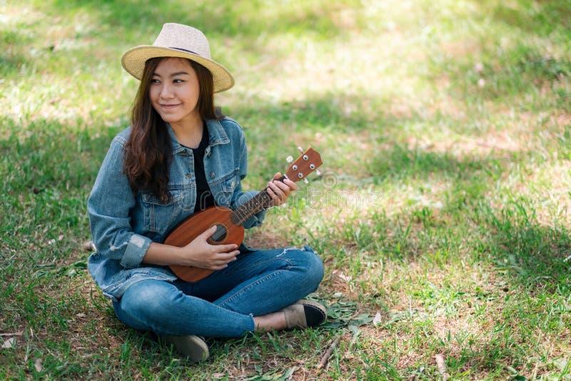 Mujer que sienta y que juega el ukelele en el aire libre fotografía de archivo libre de regalías