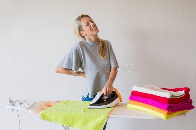 Mujer que siente espalda dolor mientras que trabaja en casa foto de archivo