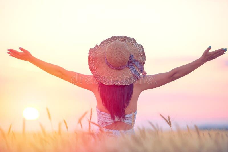 Mujer que siente libre y feliz en un ajuste natural hermoso en la puesta del sol fotos de archivo