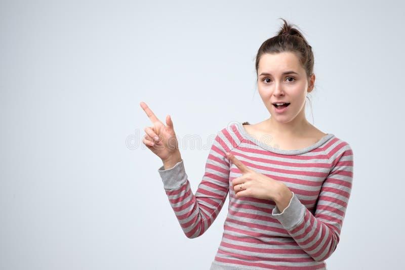 Mujer que sonríe ampliamente señalando los fingeres lejos, mostrando algo interesante foto de archivo