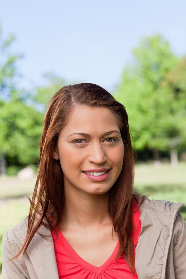 Mujer que sonríe como ella mira derecho delante de ella en un parque fotografía de archivo libre de regalías
