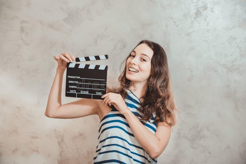 Mujer que sonríe con concepto de la audición de la película del tablero de chapaleta imagen de archivo libre de regalías