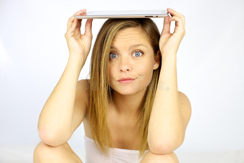 Mujer que sonríe con la tableta en su cabeza fotos de archivo libres de regalías