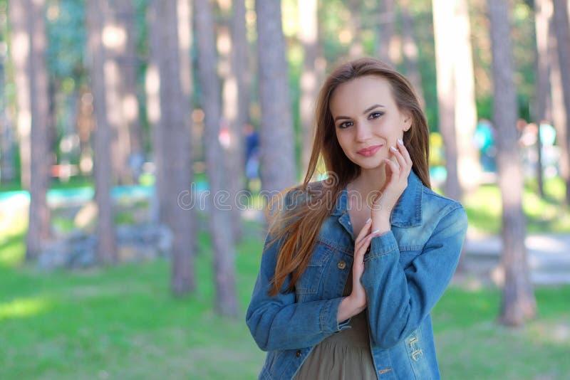 Mujer que sonríe con sonrisa perfecta en un parque y que mira la cámara foto de archivo