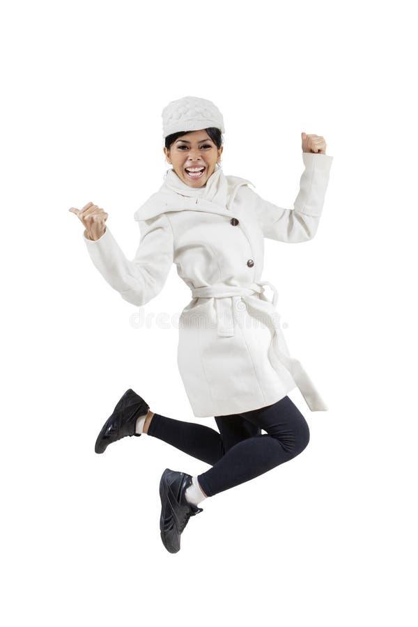 Mujer que sonríe en la cámara mientras que salta foto de archivo libre de regalías