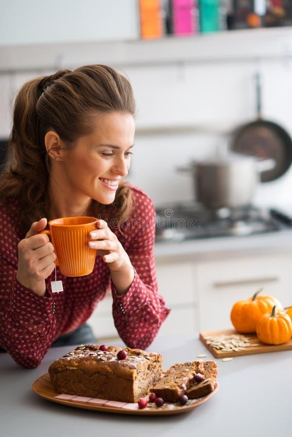 Mujer que sonríe en la cocina que sostiene la taza con el pan de la fruta fresca imagen de archivo libre de regalías