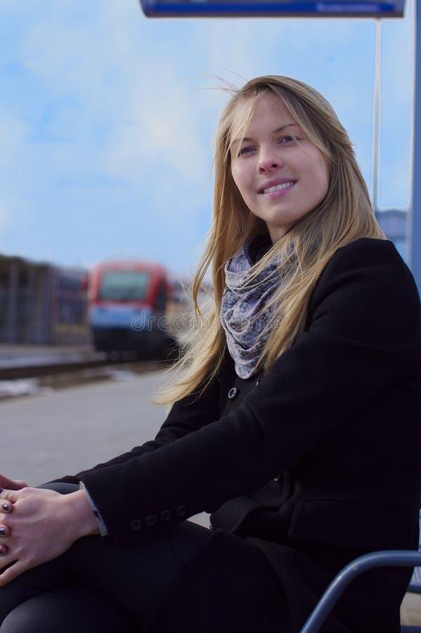 Mujer que sonríe en la estación de tren fotografía de archivo