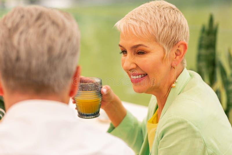 Mujer que sonríe mientras que bebe el jugo para el desayuno con el marido imagen de archivo libre de regalías