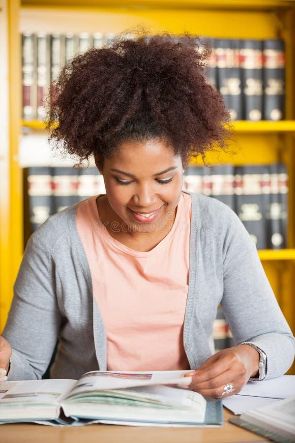 Mujer que sonríe mientras que libro de lectura en universidad fotos de archivo libres de regalías