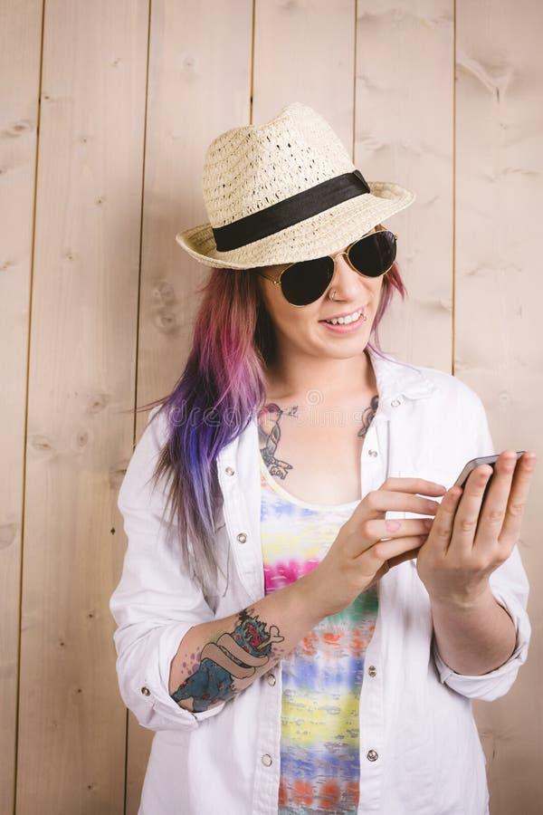 Mujer que sonríe mientras que usa el teléfono móvil fotografía de archivo