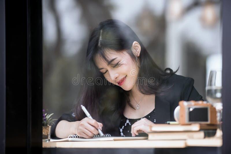 Mujer que sonríe y pluma de tenencia que señala en el libro fotos de archivo