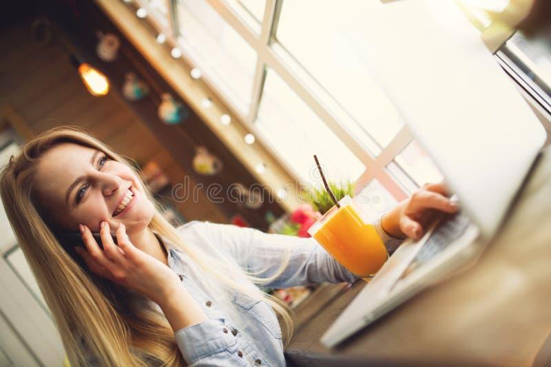 Mujer que sonríe y que habla con alguien en el teléfono que se relaja en un café de moda, sentándose en una tabla con un ordenado imagen de archivo libre de regalías