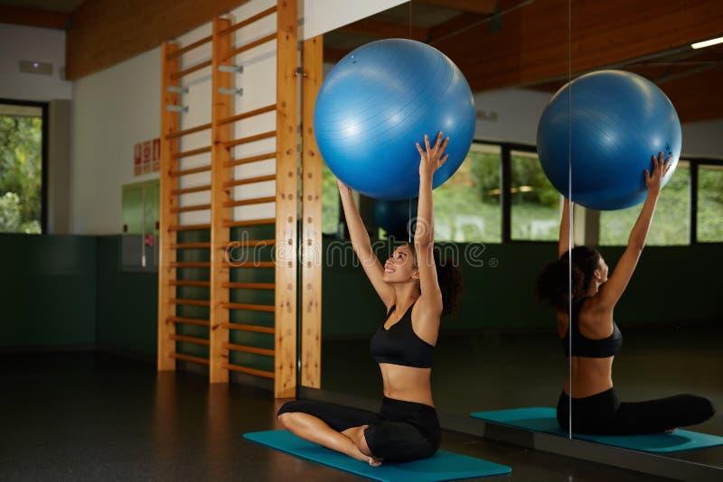 mujer que soporta la bola de Pilates y que se sienta en la estera durante su entrenamiento de la aptitud en gimnasio imágenes de archivo libres de regalías