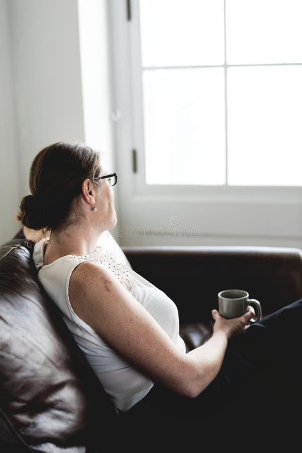 Mujer que sorbe una bebida que se sienta en un sofá imagen de archivo