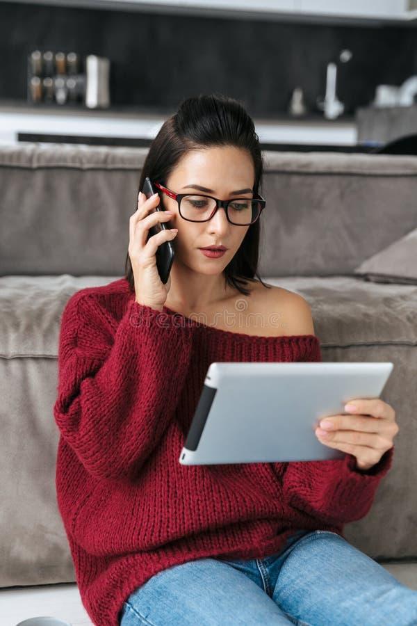 Mujer que sorprende dentro en hogar en el sofá usando la tableta que habla por el teléfono móvil fotografía de archivo libre de regalías