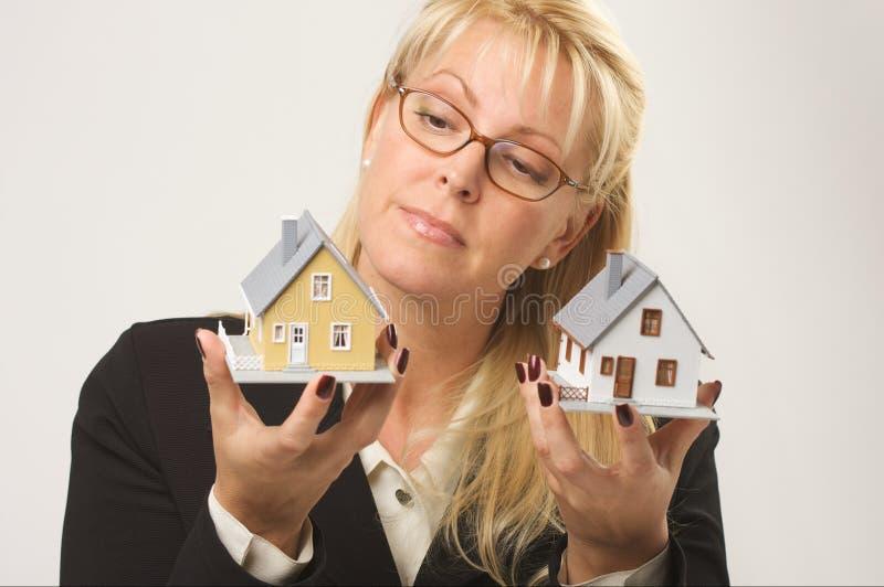 Mujer que sostiene dos casas imagen de archivo