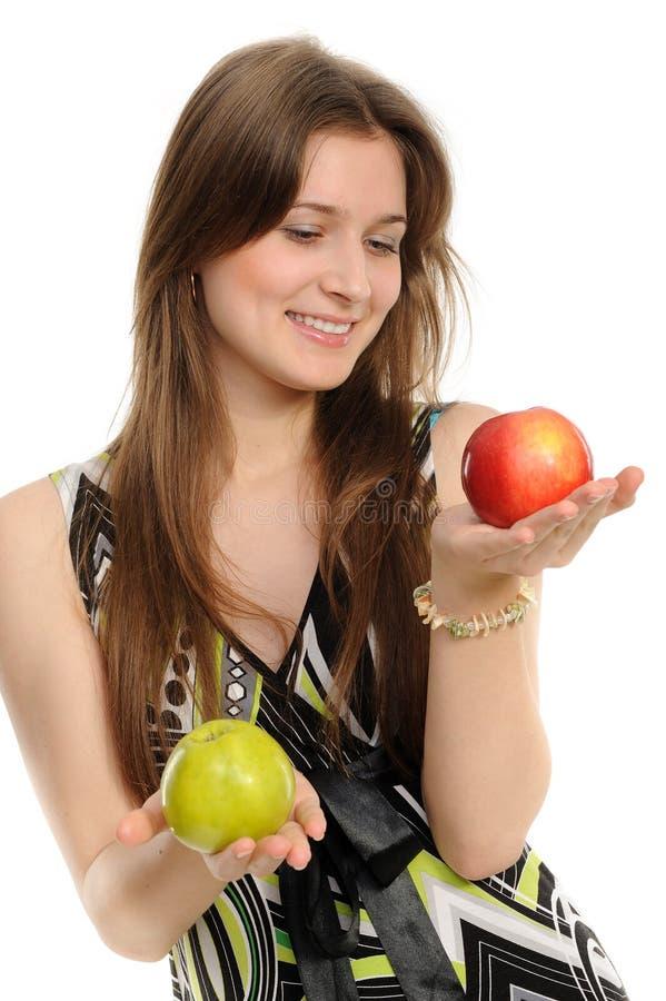 Mujer que sostiene dos manzanas foto de archivo