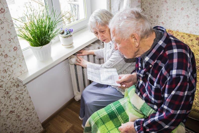 Mujer que sostiene efectivo delante del radiador de calefacción Pago para calentar en invierno Foco selectivo imagen de archivo libre de regalías