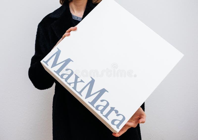 Mujer que sostiene el barco de lujo de Max Mara para la ropa fotos de archivo