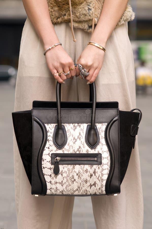 Mujer que sostiene el monedero, bolso con los anillos en los dedos imagen de archivo