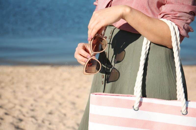 Mujer que sostiene el bolso y las gafas de sol en la playa, primer fotografía de archivo